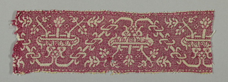 Border fragment showing a curving vine with geometric flowers in red silk on linen.