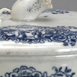 White porcelain bowl and cover with blue floral design and a decorative flower knob. Within the design, there is an image of two figures.