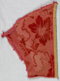 Fragment of tomato-red cut and uncut velvet. Patterned ground of uncut pile with large swinging floral design in cut pile.