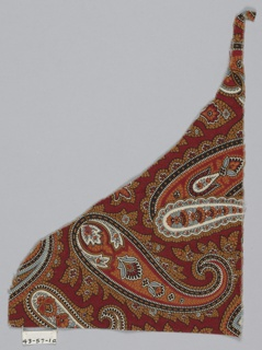 Corner fragment with a dark red ground has a paisley pattern in orange, light blue, white, black, and red.