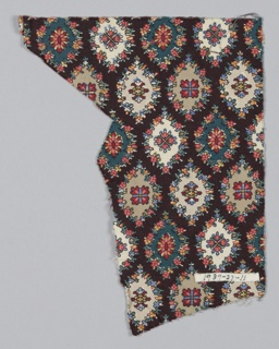 Fragment with a pattern of pointed medallions ornamented with geometric forms in bright red, blue and yellow on a brown ground.
