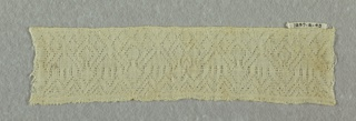 Border fragment woven in a geometric openwork pattern that resembles lace.