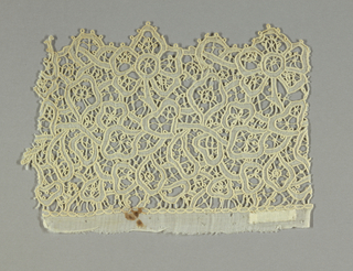 Fragment of a border has an intertwined floral vine pattern of fine white linen held with connecting bars.