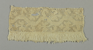 Band of cutwork in a design of an angular vine with leaves. On one side, a piece of plain white linen cloth; on the other, white fringe.