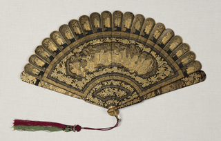 Brisé fan. Lacquered wood sticks; black ground with figures in landscape, surrounded with borders and other decorative detail exquisitely painted in two tones of gold and minute touches of vermillion. Reversible, so the in one direction, the composition seems to be thrown out of proper relation. Black silk ribbon. Red and green silk tassels. Gilt metal bail.