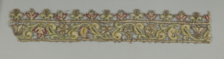 Narrow band with a scrolling leaf and flower design. Edged at top with a row of flower sprigs. Cutwork is embellished with embroidered outline of red, green, and dark yellow. Loops of metallic thread decorate edges and spaces between motifs.