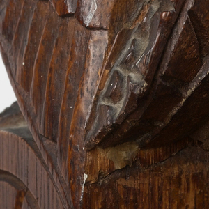 Upright rectangular form of solid oak construction; surface covered with carved and incised decoration of naturalistic and stylized floral and vegetal motifs, and geometric patterns in neo-gothic style; upper section composed of drop front writing surface that opens to reveal drawers and pigeon hole compartments; lower section is a two door cupboard surmounted by narrow drawer; another narrow drawer with open shelf above forms top of desk, a highly carved figure of an owl on each side at front. Drop front, cupboard doors, and drawers fitted with patinated, elaborately cast ornamental strap hinges, lock plates, and pulls, probably nickel-plated bronze.