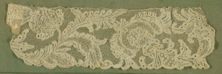 Border fragment with an elaborate conventionalized serpentine floral design. Many minute rosettes in relief. Many openwork stitches in the design. Small scallops on the the border.