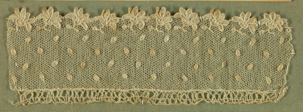 Alençon-style narrow border with lower edge in a design of minute blossoms. Ground powdered with dots.