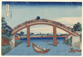This landscape view features a crowded bridge, filled with pedestrians. Below, a body of water decorated with boats and fishermen. Located on the bottom right is a man sitting on a pile of rocks, fishing, alone. In the distance, snow-covered Mt. Fuji and two pagodas. This print is from the series, Thirty-six Views of Mt. Fuji (Fugaku Sanjuroku Kei).