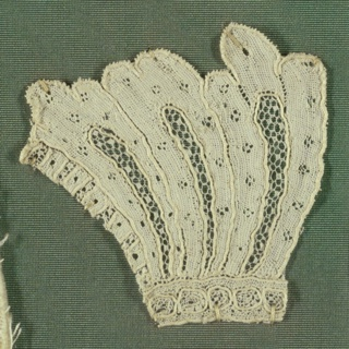 Fragment of Argentan lace showing a group of three ornamental leaves or feathers.