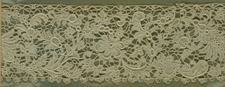 Lace fragment in a conventionalized floral pattern with parts in relief. One straight edge, the other with ornament. Fragment is mounted on a fabric-covered board and framed behind glass. Frame is natural wood.