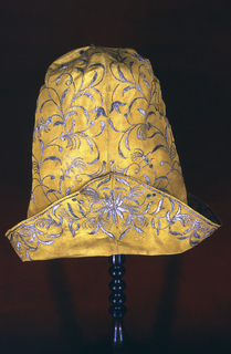 Tall man's cap of brilliant yellow silk embroidered with floral vines in silver metallic yarns. Lower edge turns up in the bicorne style.