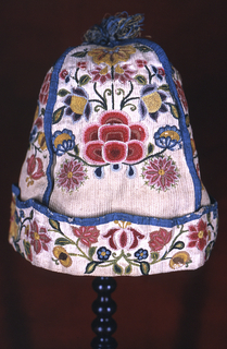 Man's nightcap made of four panels of undyed ribbed cotton with fairly deep cuff, piped along four seams and top of cuff with blue silk; topped with silk and metallic tassel.  Embroidered with bright crewel wool yarns in chain stitch with symmetrical flower spray in each panel, floral scroll along cuff.  Unlined.