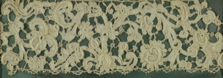Venetian point in low relief with various needlemade stitches and picots. Design of scrolling stem with leaves and flowers.