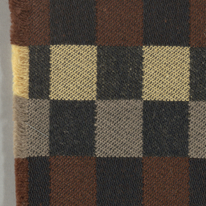 Black warp with brown, tan/grey, and yellow/tan wefts, alternating color every inch to form checked pattern. Serged on 2 sides and cut on 2 sides.