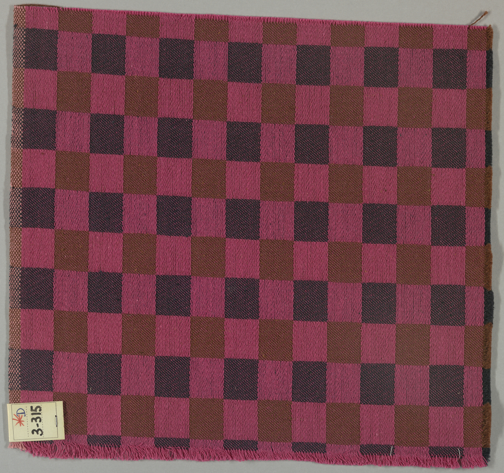 Pink warps with navy and brown wefts, alternating color every inch to form checked pattern. Selvedge on one side and cut on three sides.