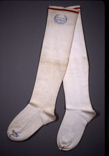 """Pair of white stockings with red lines at the top, toes and heels. On one at the top, a blue stamp of an open wreath with """"Patent Four Thread"""" in the center. On same stocking at the toe, """"British 9 in."""""""
