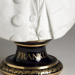 A bust portrait of Benjamin Franklin in biscuit porcelain on a gilded underglaze-blue waisted socle.
