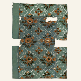 Shaped squarish figures form a checker board or diamond trellis pattern, enclosing a simple floral form on dotted ground, which alternates with floral sprays. At left, original margin of paper. Original colors appear along edges, where paper has been folded. Paper is gray and coarse; green colors have high gloss. This wallpaper was formerly used as a book cover.