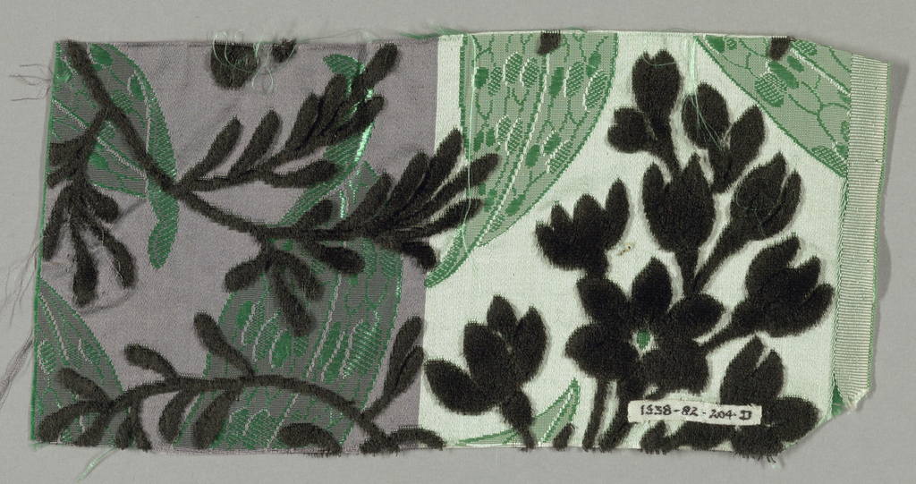 Sample with a satin ground has an allover large scale design of long, pointed leaves patterned with ovals. Over the ground is black cut velvet design of sprigs of fresia-like flowers. Pile warp cut away in pile in voided areas.
