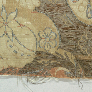 Fragment of a continuous symmetrical pattern of a palmette with leafy forms and flowers. Primarily cream-colored with tarnished gold metallic thread and grey and pale orange silk.