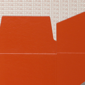 Unfolded box in orange-red.  Imprinted diagonally across front and back sides of box  (overlapping onto the box top and short sides), in silver horizontal stripes: IBM; in black: High Yield/Correctable/Film Ribbon; on underside of box; in white:  High yield Correctable film ribbon/Ruban Corrigible de grande capacité/Korrekturfänges Plasticontrast-Farbband besonders ergiebig/Cinta Correctora de mayor rendimiento; on narrow short side of box, in white horizontal stripes:  IMB; in black:  High yield Correctiable film ribbon/Ruban Corrigible de frande capacité/Korrekturfänges Plasticontrast-Farbband besonders ergiebig/Cinta Correctora de mayor rendimiento; on other narrow side of box, in black (reading from top to bottom and left to right:  (in bracket) Redorder No.:/No. de commande:/Bestellnummer:/Redordene No.: 1299 095 / (in bracket) Quantity:/Quantité: Ansahl: Cantidad:  6/; Color: black/Couleur: noir/Farbe: schwarz/Color: negro/; Not recommended for direct image offset/masters or nefotiable instruments./Ruban déconseillé pour la frappe des/cliché direct offset et des documents/bancaires et contractuels./Nicht sum Beschriften von Offset-Folien/nicht dokumentenecht./No se recomienda para usar en impresión sovre offset masters o documentos/negociables. Interior of box, in repeating pattern, in red: IBM.