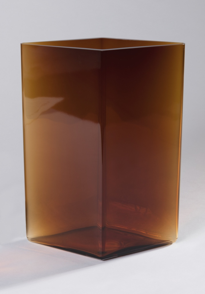 Tall diamond shaped copper-toned body of transparent glass.