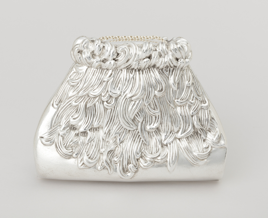 Silver square evening purse with a gilt silver interior and curved and tapering edges to the top. Decoration of chrysanthemum blossoms gather at the top and cover both sides. Purse has a removable mesh chain and mesh brackets that allow the purse to smoothly open and close.