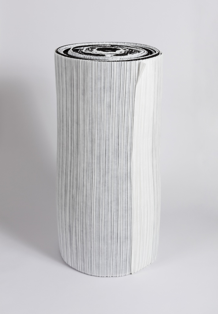 Cylindrical roll of pleated white paper resting in upright position.