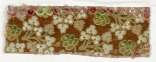 Fragment of cut and uncut velvet in a design of white flowers and green leaves against dark red cut velvet ground.