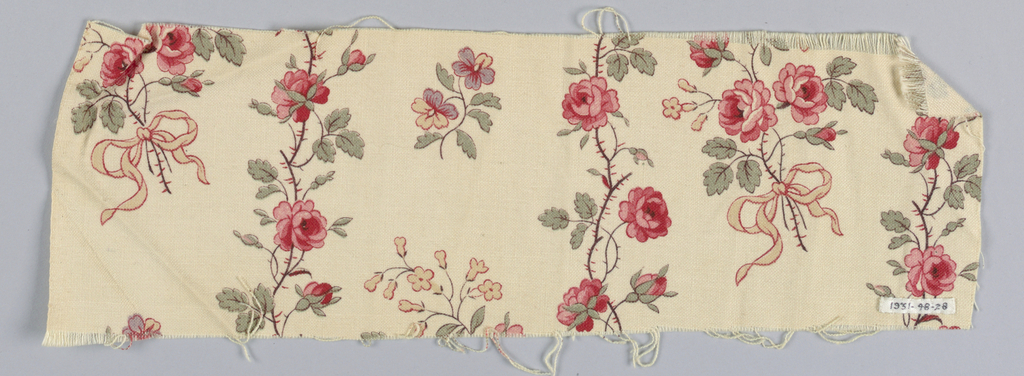Ivory ground showing a small-scale design of rose serpentines alternating with sprays of roses. Printed in red, rose, yellow, blue, brown, and gray-brown. Left selvage present.