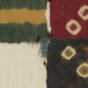 Fragment from large mantle with woven stepped sections meeting joined by warp interlocking and stitching in the weft direction. Each individual piece is patterned by tied-resist dying, creating patterns of small and large diamonds. In yellow on green, white on red, and white and rust on dark brown grounds.