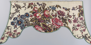Shaped window valance with sharply pointed outer corners. Fabric pattern is a polychrome design of flowers and fruit; roses, grapes, currants, pomegranates etc. in black, blue, three reds, two purples and brown. Valance is lined, interlined and bound with deep green ribbon.