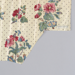 Irregularly-shaped piece of off-white cotton printed with an open pattern of multi-colored bouquets. Background dotted with small brown diamond motif.