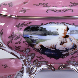 Tureen (a) of bulging and lobed oval form with two scrolling loop handles at either side and four scrolled feet; the white body with pink ground decorated at front and back with large central cartouches showing the artist as Madame de Pompadour in low-cut bodice and wig of silvery curls, with landscape in background; the pink surface embellished with platinum scrollwork and floral sprays, the flower buds rendered as fish; the articulated surfaces of the white handles and feet also picked out with platinum. Interior of bowl white, the floor decorated with scene of fish lying among ropes of pearls, all resting on soft folds of blue fabric. The domed and lobed cover (b), with pink ground decorated with platinum scrollwork and floral sprays as on tureen, and having central knob in the form of large platinum-colored flower buds with white and platinum leaves. The platter (c) of roughly oval shape having a white rectangular well, and wide everted rim, its two scrolled ends forming handles, and decorated with images of the artist as Madame de Pompadour; the articulated surface with pink ground, picked out with platinum scrollwork and floral sprays as on tureen.