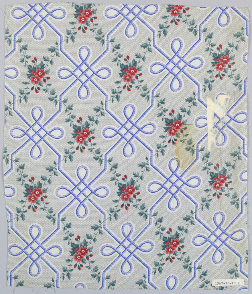 """Two pieces, same design, different colors. A) ground printed by """"molette"""" in minute grey zig-zag, leaving white areas through which pass a design of long interlace in brown, forming trellis pattern. Clusters of little flowers in red (strawberry) blossoms and green foliage printed within trellis pattern, possibly by block or surface roller. B) same design, but interlace in blue. Glazed."""