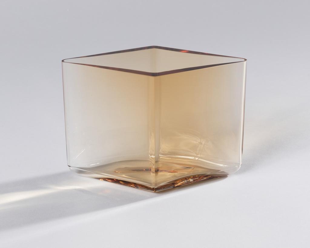 Short diamond shaped beige-toned body of transparent glass.