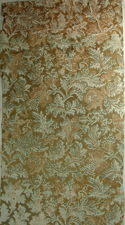 All-over pattern of large-scale leaves and flowers. Printed in greens and salmon on ochre ground.