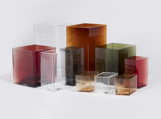 Group of modular diamond-shaped transparent glass vases of varying hights and colors (copper, red, gray, green, pale pink, and uncolored).