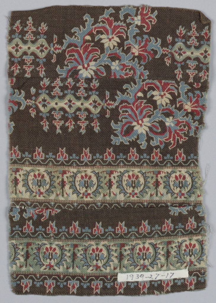 Fragment with conventionalized floral ornament on a brown ground with border; in red, blue, green and white.