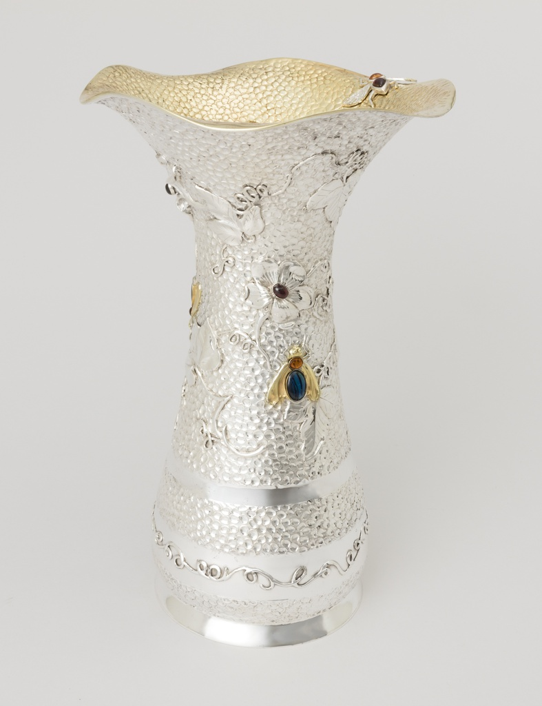 Vase with a silver exterior and silver gilt interior of a flaring form with a repoussé-like finish. Vase has an undulating top edge and the body is decorated in natural motifs including bees and flowers.