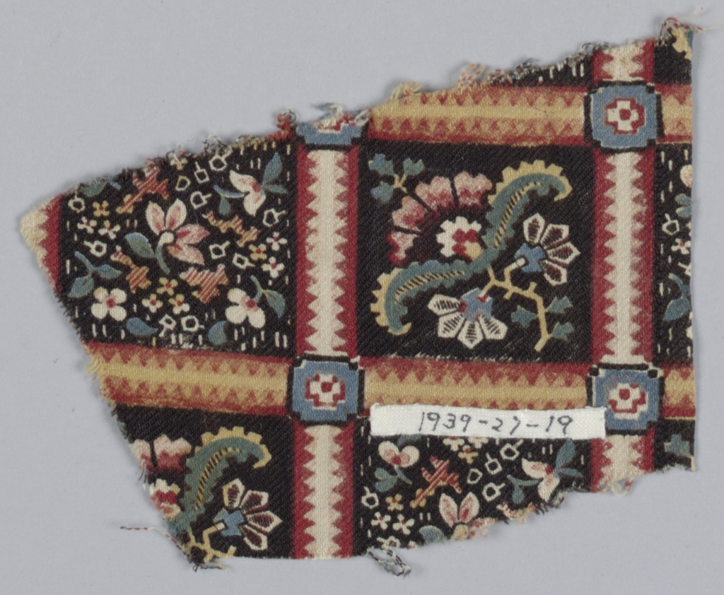 Fragment with a square grid filled with multicolored flowers on a black ground. Grid is formed by bands brownish-red decorated with sawtooth stripes in white and yellow.