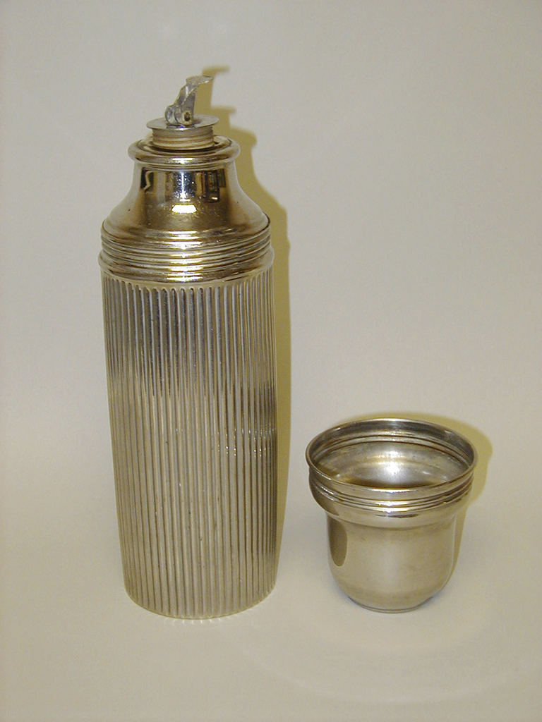 Cylindrical, fluted metal body, horizontal ridges at top; tapering, flat-topped, cylindrical metal cup inverted over bottle mouth to serve as cap;  cap unscrews and lifts off to reveal small cylindrical rubber stopper, with circular metal top and hinged togle latch, set snuggly into circular mouth of interior glass vacuum bottle.
