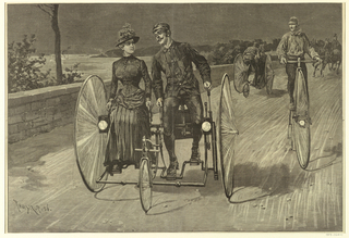 A man and woman seated side by side ride a wide bicycle vehicle with two large wheels at either side and a small wheel at the front. The couple appears to be in conversation while riding along the Hudson River, which is visible at left. At right, behind the couple, a man rides a tall pennyfarthing bicycle. Further in the background, another couple rides a bicycle in yet a different style. In the background, at right, a coachman visible behind two horses.