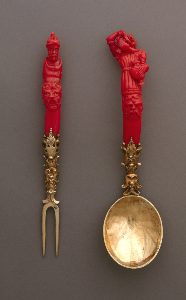 Two-tined pointed fork with sloping shoulders. Gilded neck elaborately decorated with leaves, masks and scrollwork. Slightly curved handle of red coral, carved with a grotesque head on the front, above it a torso and head of a man wearing a helmet. Back of handle carved in decorative pattern.