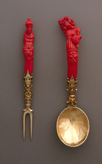 Oval spoon bowl, gilded neck elaborately decorated with leaves, masks and scrollwork. Slightly curving handle of red coral, carved with a grotesque head on the front, above the upper body of a woman holding a ewer in one hand and an urn in the other, as if pouring liquid from one into the other. Back of handle has decorative pattern.