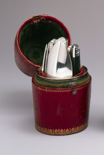 Red leather holder with tooled gold borders and velvet lining, enclosiing a silver cup with fitted velvet-lines mount inside holding five implements: folding knife with steel blade and ebony handle, silver fork and spoon  with ebony handle; holder fits into silver cup within case.