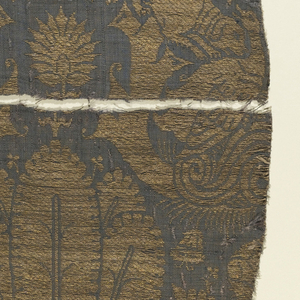 Purplish-gray ground with design entirely in gold. Pattern arranged in offset horizontal rows. Paired hound attacking goose separated by broad curving branches and palm leaves; small blossoms in interspaces.