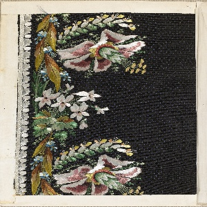 Black uncut voided velvet with a ground of small blue dots embroidered in a border design of large flowers in colored silks.